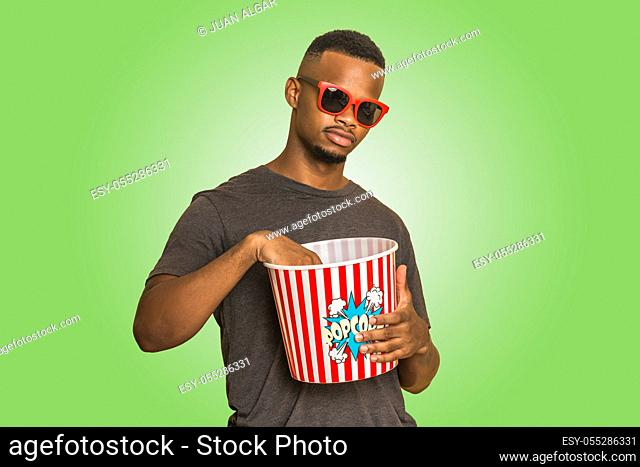 Young African American guy in trendy sunglasses eating popcorn from bucket while standing against green background