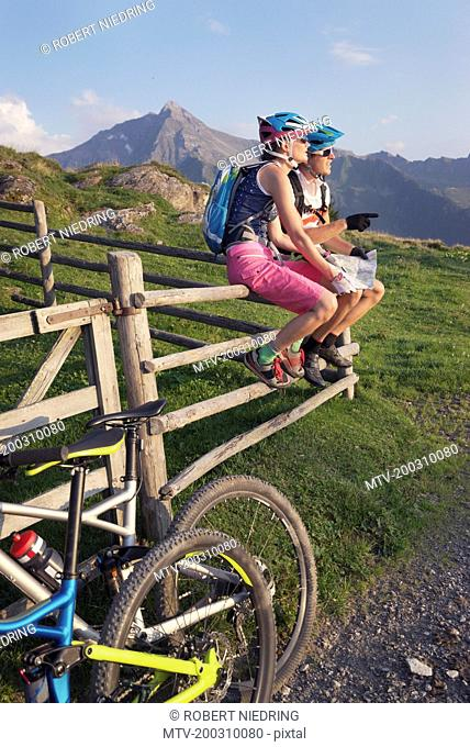 Young couple of mountain bikers with map sitting on wooden fence, Zillertal, Tyrol, Austria