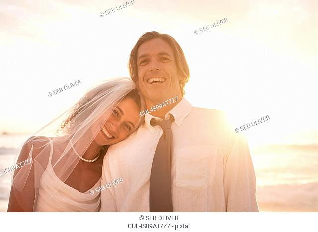 Bride leaning on groom's shoulder on beach against sunset