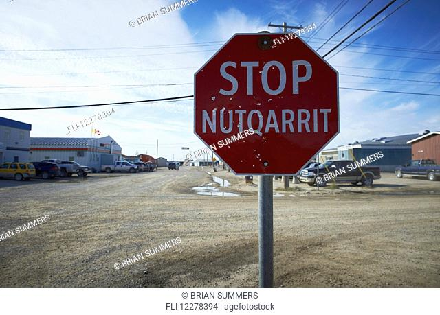 Stop sign at intersection on dirt road; Cambridge Bay, Victoria Island, Nunavut, Canada