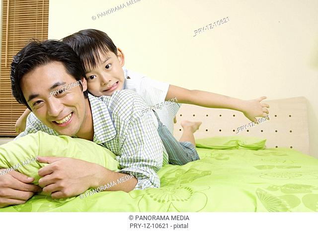 Son riding on father on bed