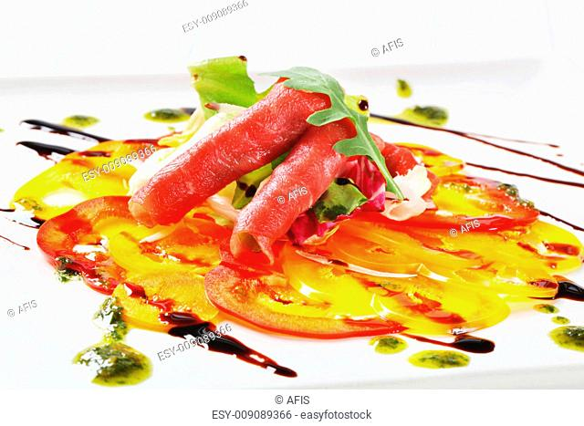 Thinly sliced bell peppers and raw beef garnished with pesto and balsamic vinegar