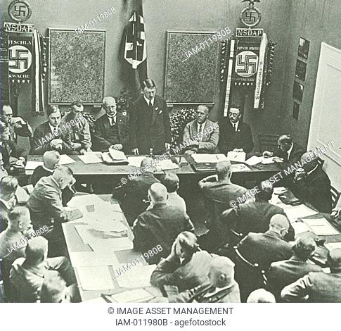 Hitler in Munich adressing a meeting of the NSDAP in 1925. Third to the left of Hitler is Alfred Rosenberg, on the right are Gregor Strasser and Heinrich...