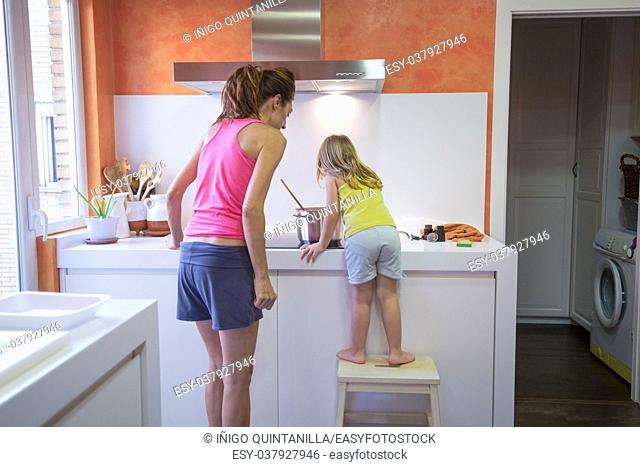 Funny scene. Four years old blonde child climb on stool o ladder cooking in vitroceramic or electric stove with a saucepan, next to woman supervising