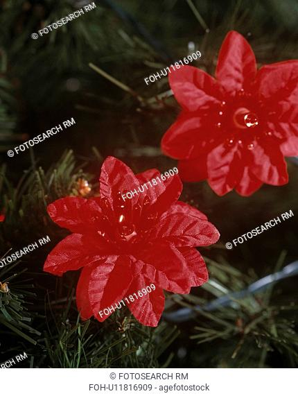 Close-up of red faux poinsettia flowers on Christmas tree