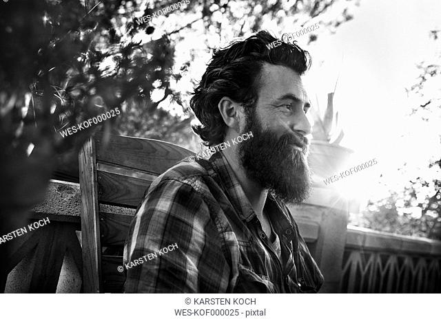 Smiling man with full beard on porch