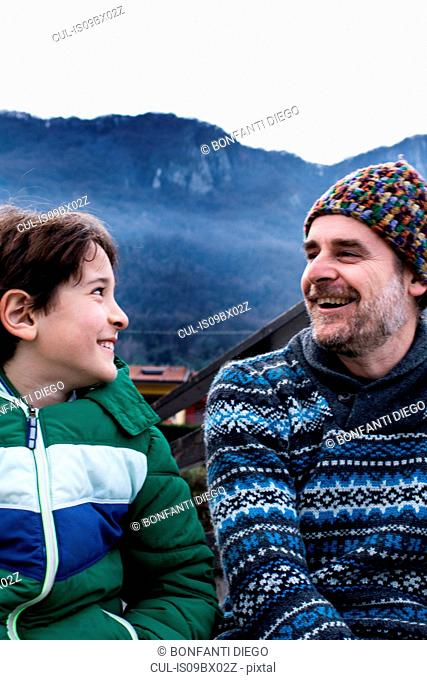 Boy and father looking at each other on lakeside pier, Lake Como, Onno, Lombardy, Italy