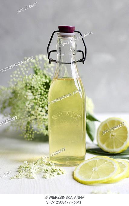 Elderflower cordial in a vintage bottle, with fresh elderflowers and lemon in the background