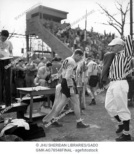 Johns Hopkins Co-captain and attackman Byron Forbush (no, 1951. 47) stands on the sidelines next to a referee during a game, with spectators in the background