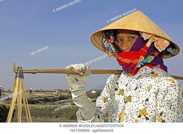 Woman salt worker in conical hat with pannier baskets on shoulder salt ponds Phan Thiet Vietnam
