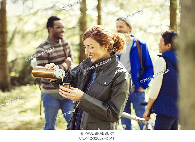Smiling woman hiking pouring coffee from insulated drink container in woods
