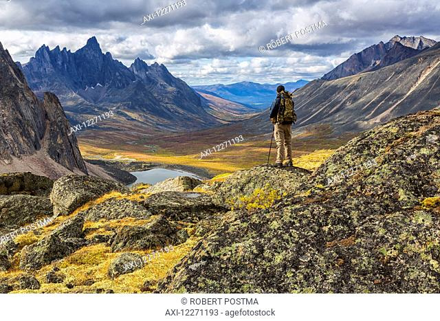 Hiker standing on a rock overlooking the colourful valleys in Tombstone Territorial Park in autumn; Yukon, Canada