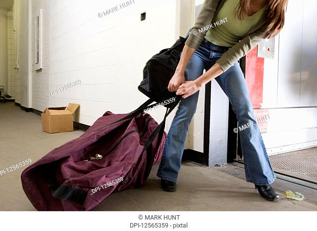 Young woman pulling a huge traveling bag