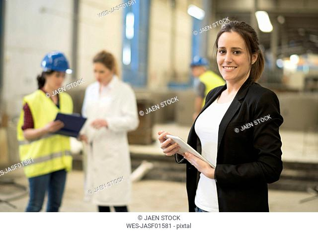 Young female entrepreneur doing check up in factory