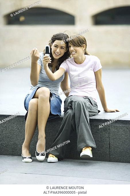 Teen girls taking photo together with cell phone