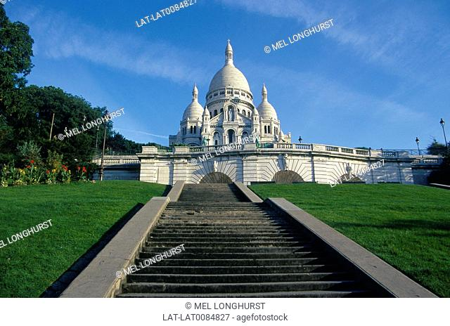 Sacre Coeur. White domed church on top of hill. Against blue sky. Steps