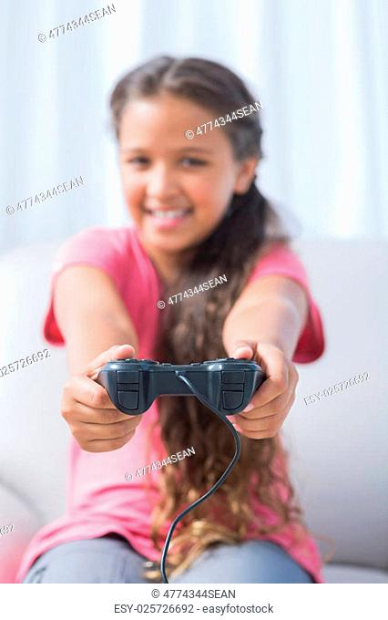 Happy girl playing video game on sofa in home