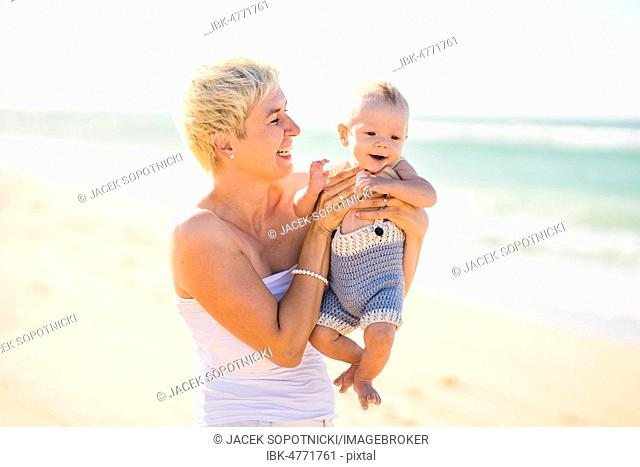Attractive blond mother with 4 months old baby boy on the beach, Portugal