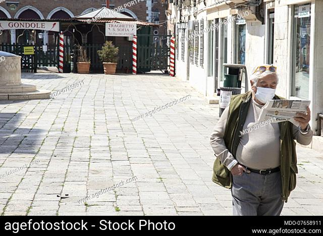 A gentleman with a protective mask while reading the newspaper on the day of the patron saint of San Marco during the lockdown due to the Coronavirus pandemic...