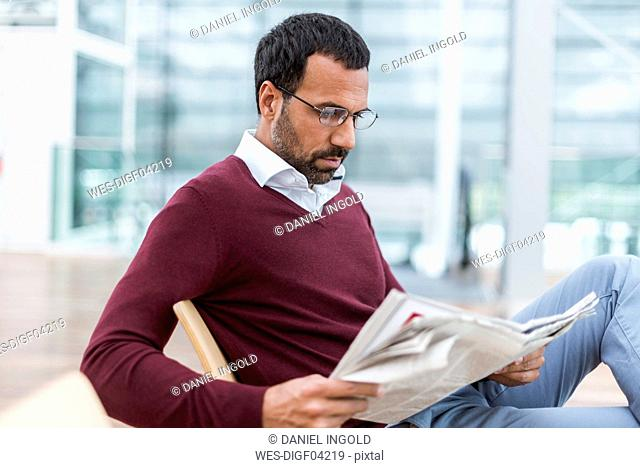 Businessman reading a newspaper in waiting hall