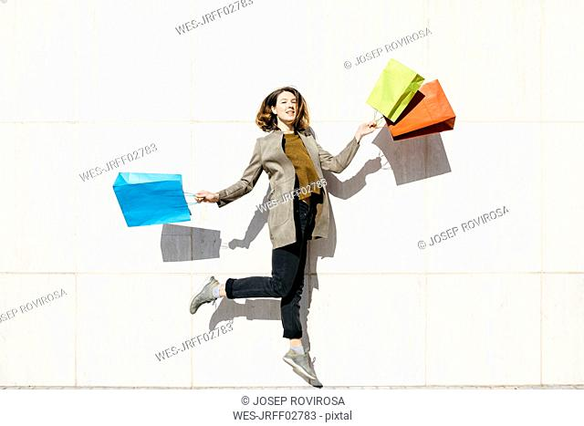 Cheerful woman with shopping bags jumping at a wall