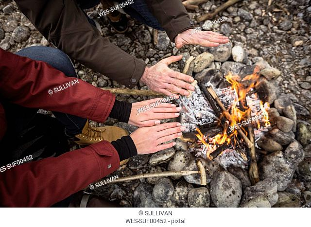 Close-up of couple warming hands at camp fire