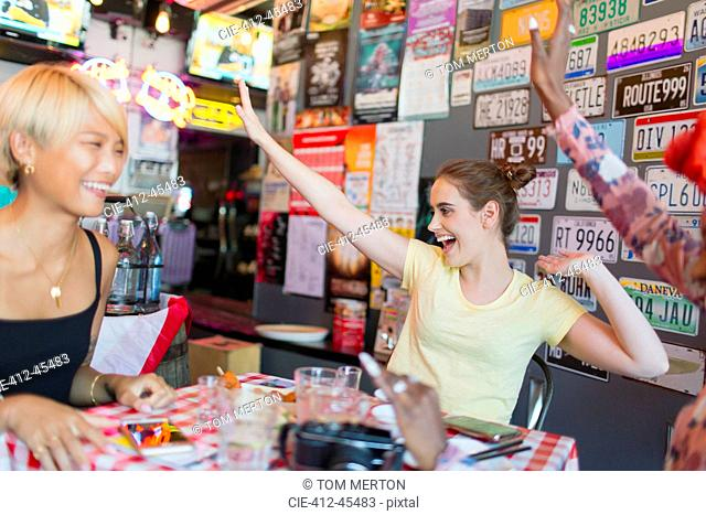 Enthusiastic young women friends cheering in bar