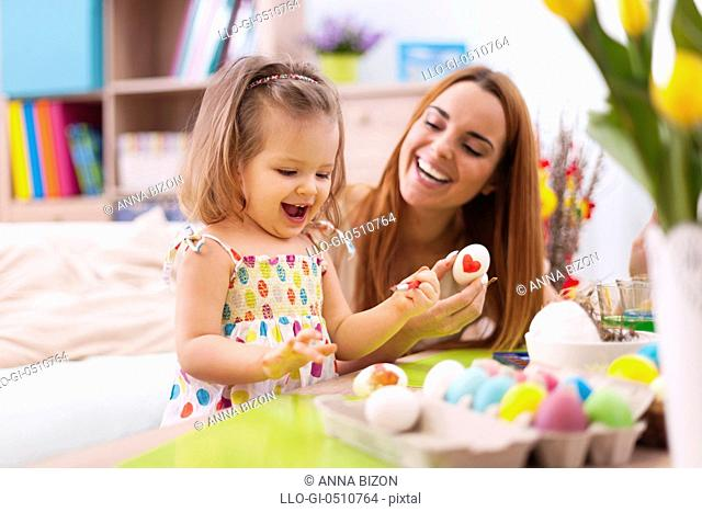 Loving mother and her baby painting easter eggs. Debica, Poland
