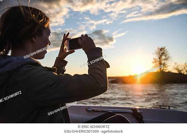 Young Adult Woman in Boat Taking Pictures of Lake at Sunset