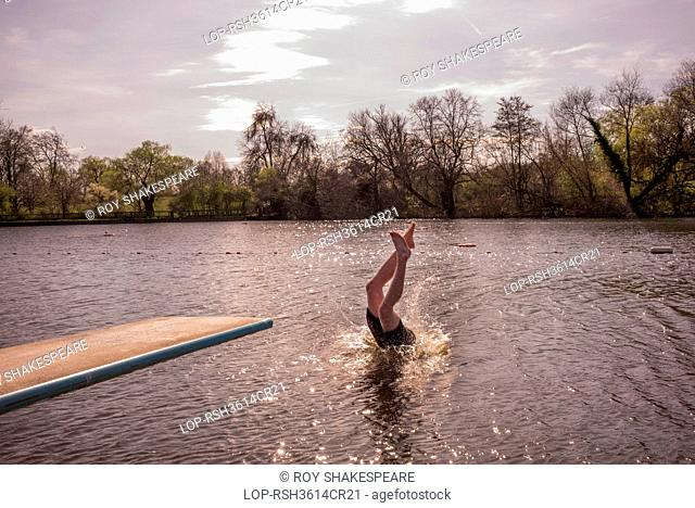 England, London, Hampstead Heath. A young man swimming in spring fresh water ponds