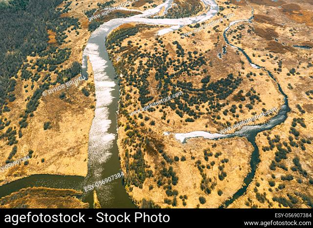Aerial View Curved River In Early Spring Landscape. River bends Curves and dry grass landscape. Top View Of Beautiful European Nature From High Attitude