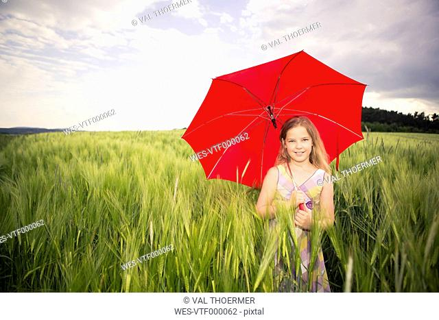 Germany, teenage girl with red umbrella standing in a corn field