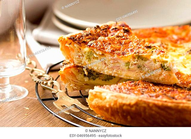 Quiche, french vegetable pie. Slice of quiche cut out from the whole pie. Set against background of plate stack and wine glass