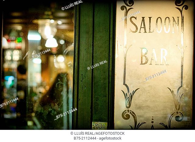 Carved and decorated glass door of a pub with the words Saloon, Bar and Pull in Hampstead, London, England, UK, Europe