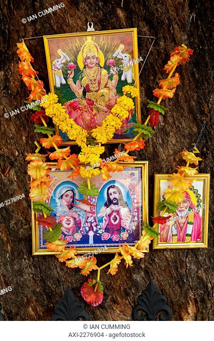 Jesus and Virgin Mary picture with Hindu god with garlands of flowers on tree; Goa, India