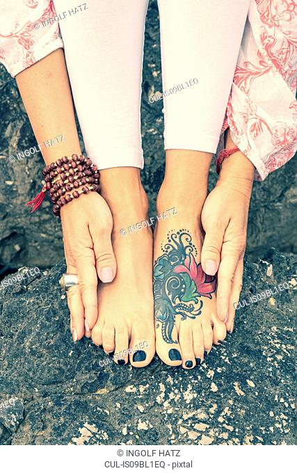 Woman touching tattooed feet with hands