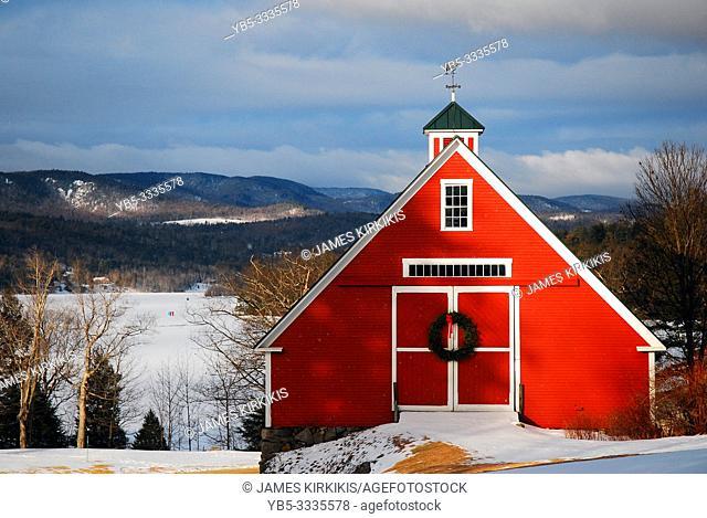 A Christmas wreath hands on a New England barn