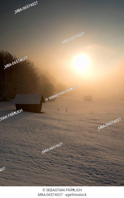 Hut in snow-covered alpine winter landscape close Garmisch Partenkirchen. In the background the rising sun in the morning fog with other wooden huts