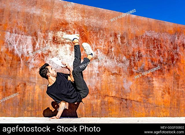 Man with face mask doing handstand against wall