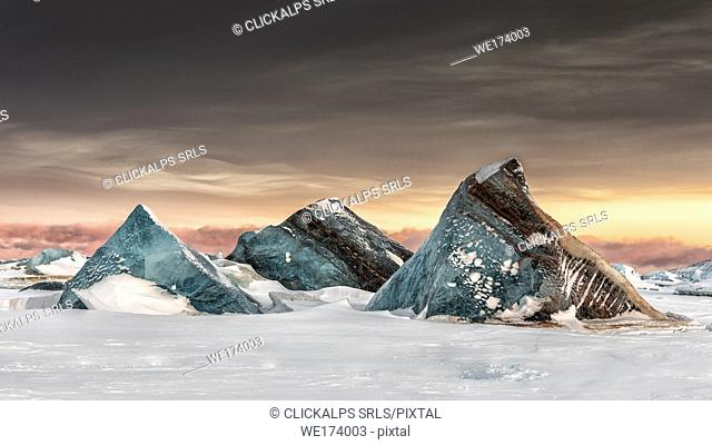 Icebergs on the sea ice off Spitsbergen east coast, Svalbard, entrapped in the fast ice