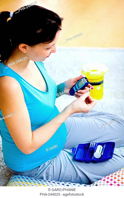 A diabetic pregnant woman is checking her blood sugar level self glycemia. A drop of blood obtained with a pen-like lancing device is placed on a test stick and...