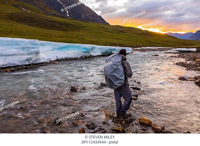 A backpacker observes the midnight sun peeking through the clouds from an unnamed fork of the Atigun River still partially covered in aufeis (sheet-like ice...