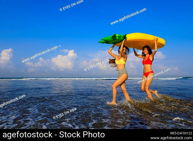 Cheerful female friends carrying pineapple float on head while enjoying at beach during vacation