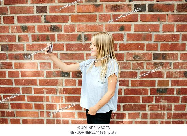 Girl with cell phone taking selfie