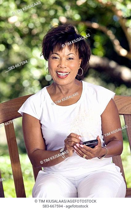 Senior woman sing a PDA or Blackberry phone