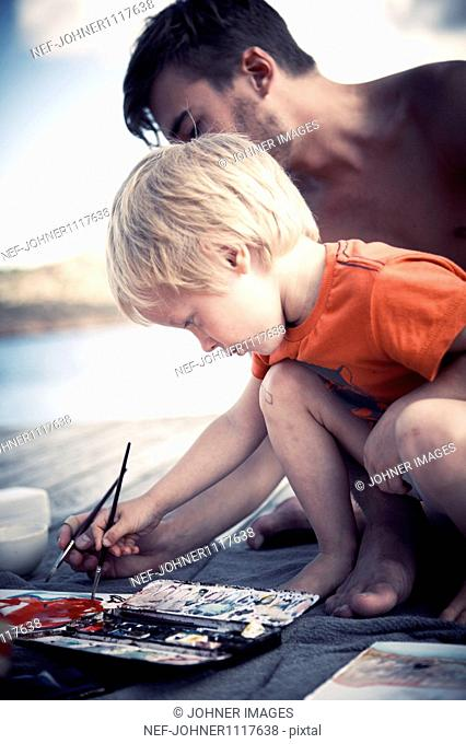 Boy painting with brother on jetty