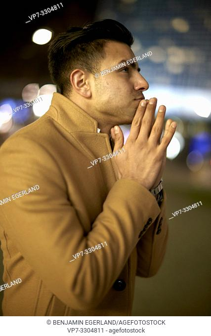 young Afghan man with folded hands at night, in Berlin, Germany