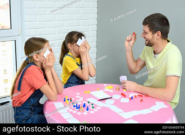 Dad and daughters play board games at home