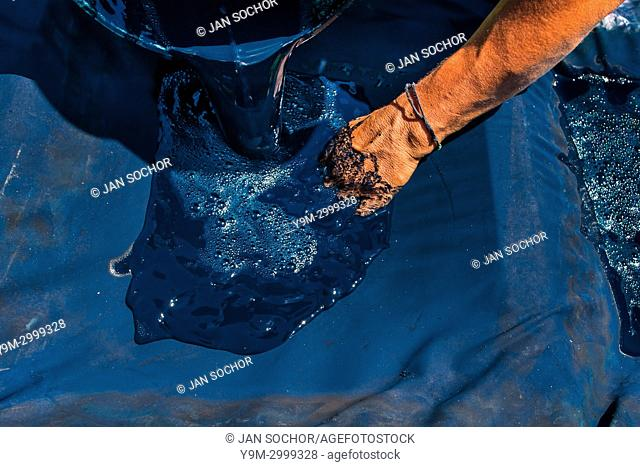 Miguel Ventura, a Salvadoran natural indigo producer, pours liquid indigo solution onto a cloth sheet to filter out the water at the semi-industrial manufacture...