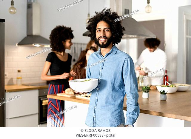Friends preparing dinner party in the kitchen, man serving salad